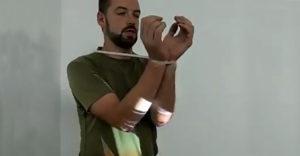 A férfi bemutatja, hogyan lehet a kezeidet gyorsan kiszabadítani a gyorskötözőből