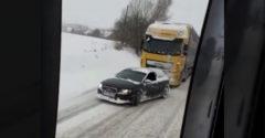 A kis Audi elvontatott egy kamiont a hófödte emelkedőn. (Lengyelország)
